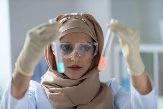 Lenço de cabeça elegante. química linda de olhos escuros usando um lenço estiloso segurando tubos de ensaio com produtos químicos
