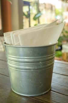 Lenço de papel no balde na mesa de madeira
