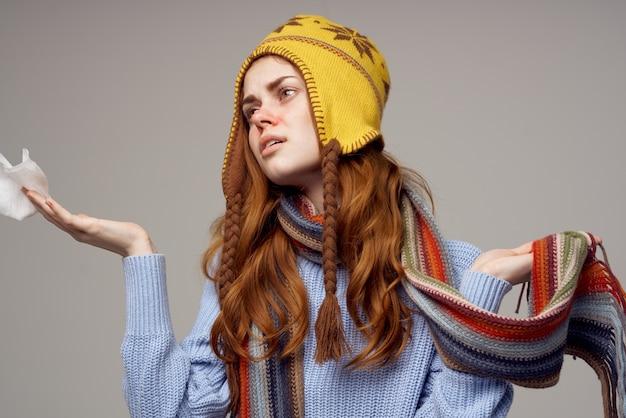 Lenço de pescoço ruivo de mulher com chapéu na cabeça e luz de fundo