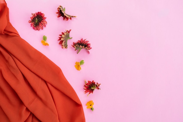 Lenço laranja, folhas vermelhas e flores amarelas isoladas em fundo rosa, ideia de conceito mínimo.