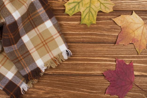 Lenço xadrez acolhedor e folhas de bordo de outono