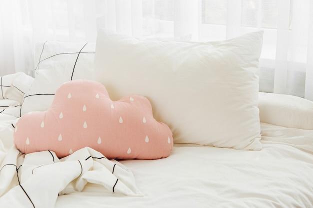 Lençóis brancos com cobertor listrado e travesseiro brilhante. cama bagunçada.