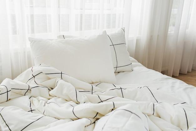Lençóis brancos com cobertor listrado e travesseiro. cama bagunçada.