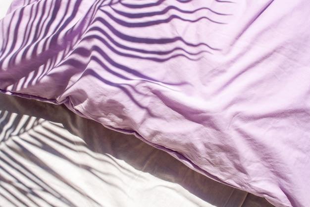 Lençóis brancos e travesseiros lilases. têxteis naturais. tendências em sombras contrastantes com folhas de palmeira