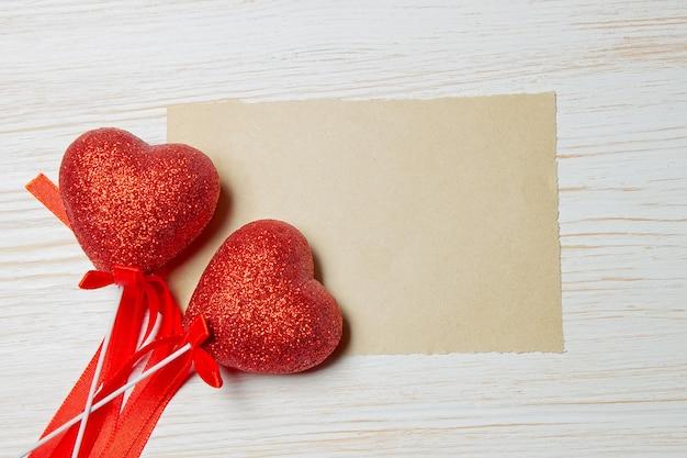 Lençol branco com dois corações vermelhos de dia dos namorados encontra-se no fundo branco de madeira. plano de fundo do feriado, plano com espaço para texto