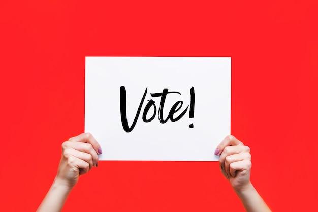 Lençol branco com o slogan vote em mãos femininas isoladas em uma parede de cor vermelha