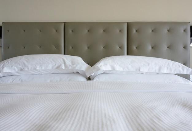 Lençol branco e travesseiro com cabeça de cama de cor cinza estilo clássico no fundo da parede