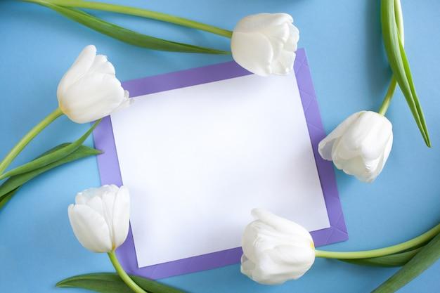 Lençol branco no quadro lilás e tulipas brancas em torno dele sobre fundo azul.