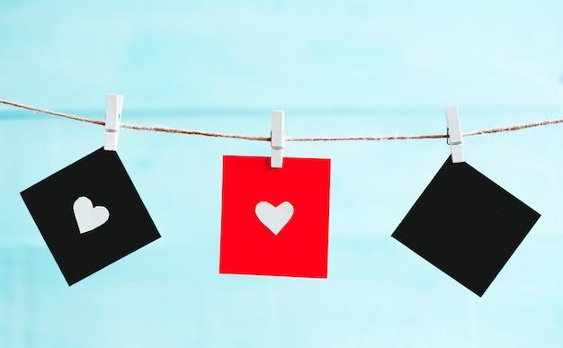 Lençol preto e vermelho com o coração espalhado sobre uma corda sobre fundo azul. plano de fundo dia dos namorados.