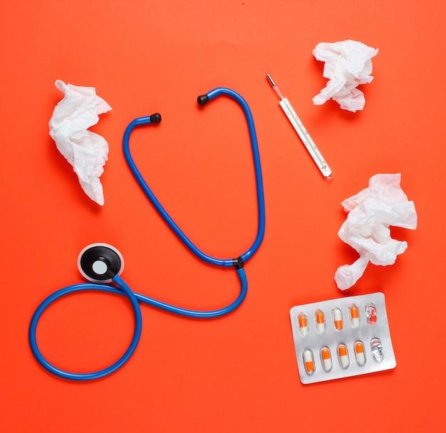 Lenços nasais usados, termômetro, pílulas, estetoscópio