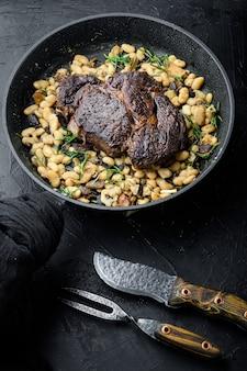 Lendária costela grelhada com feijão, em frigideira de ferro fundido, com garfo e faca de carne, em mesa de pedra preta