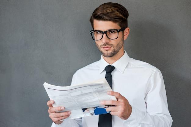 Lendo algumas notícias de negócios. jovem confiante de camisa e gravata segurando o jornal