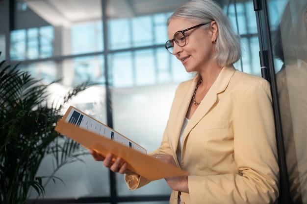 Lendo documentos. vista lateral de uma mulher de negócios caucasiana concentrada na casa dos 50 anos lendo documentos em uma pasta de papel enquanto encostada em uma parede de vidro