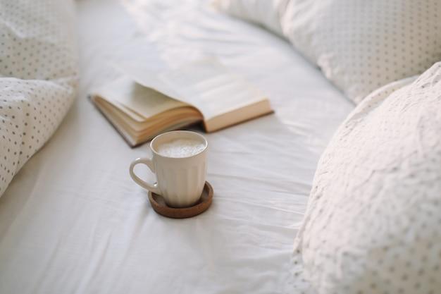 Lendo e tomando café da manhã na cama. xícara de café e um livro na cama. aconchegante manhã de sol em casa.