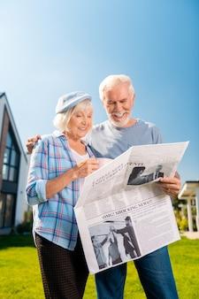 Lendo jornal. casal de idosos saindo de casa enquanto lêem jornal