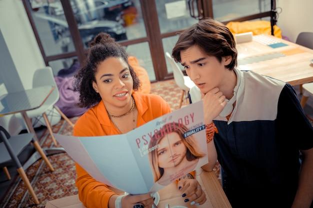 Lendo juntos. um menino e uma menina lendo a revista juntos