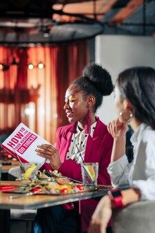 Lendo livro mulher bonita afro-americana usando acessórios brilhantes lendo livro
