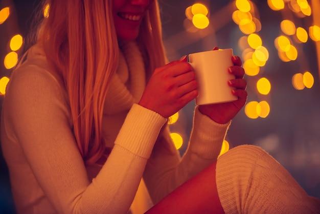 Lendo mensagem adorável dele. close-up de uma jovem bonita com um suéter branco segurando uma xícara de café e sorrindo com luzes de natal desfocadas no fundo