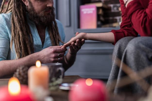 Lendo o futuro. close-up de uma palma feminina em mãos masculinas durante a sessão de leitura da sorte