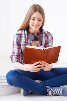 Lendo seu livro favorito. linda garota adolescente lendo um livro e sorrindo enquanto está sentada dentro de casa