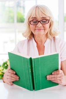 Lendo seu livro favorito. mulher sênior lendo um livro e sorrindo enquanto está sentada à mesa