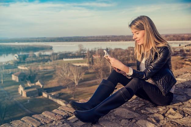 Lendo um conceito de livro, leitura de mulher loira relaxada, paisagem em segundo plano. feliz menina loira sentada e lendo um livro