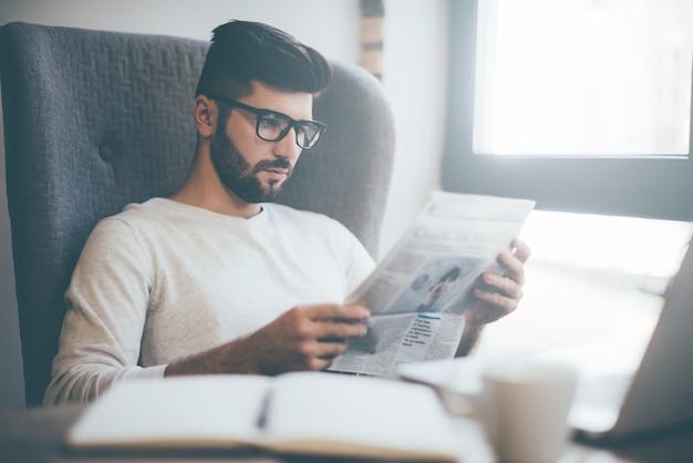 Lendo um jornal novo. jovem confiante usando óculos lendo jornal