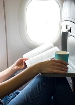 Lendo um livro e segurando uma xícara