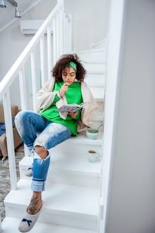 Lendo um livro interessante. mulher agradável e incomum deitada nas escadas de seu apartamento duplex e ocupando a mente com o enredo do livro