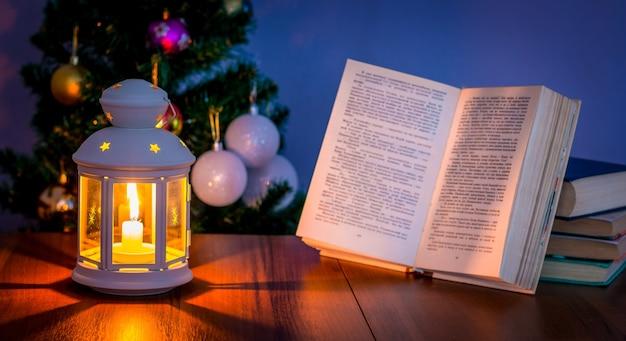 Lendo um livro no inverno perto da árvore de natal à luz de uma lanterna com uma vela_