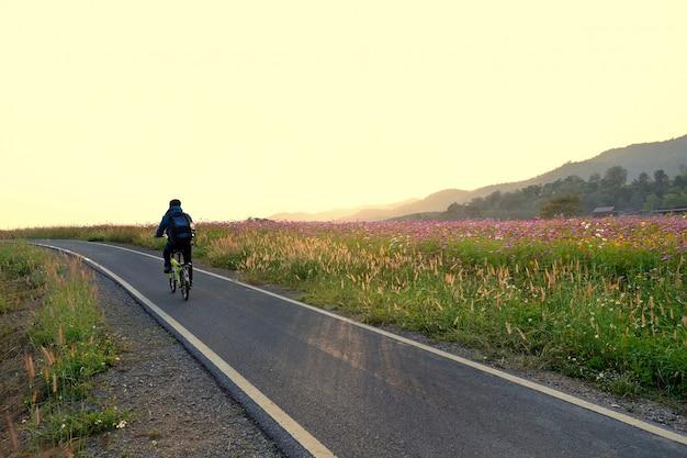 Lene de bicicleta na paisagem de estrada e flores