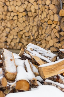Lenha fica sob a neve. lenha para a lareira e fogão