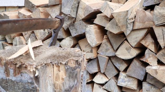 Lenha lascada para o inverno para aquecimento. o machado é cravado com uma lâmina no toco. cutelo com cabo de madeira. colheita na fazenda. lenha seca empilhada em pilhas para aquecer uma casa.