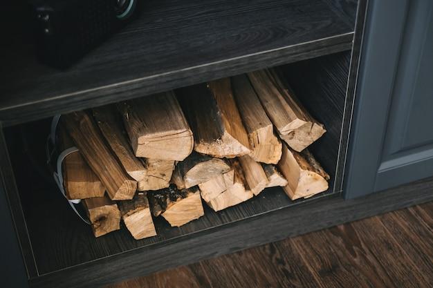Lenha para lareira em uma prateleira de madeira na cozinha, close-up.