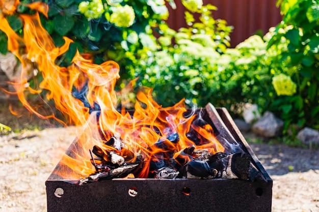 Lenha queimando na grelha. descanse na natureza. carvões quentes. fogo de fogueira.