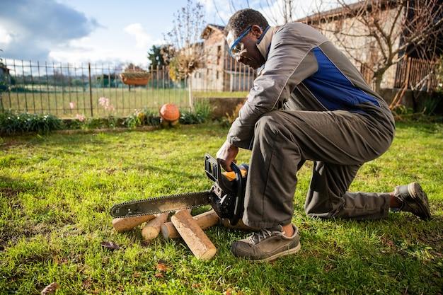 Lenhador africano de joelhos corta pedaços de madeira com sua motosserra