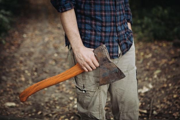Lenhador barbudo forte segurando um machado na floresta