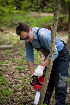 Lenhador de macacão e óculos trabalha com motosserra e serrando uma árvore na floresta
