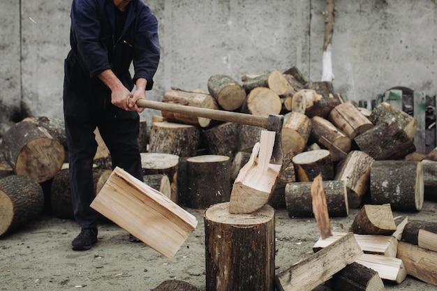 Lenhador forte cortar madeira com um machado afiado
