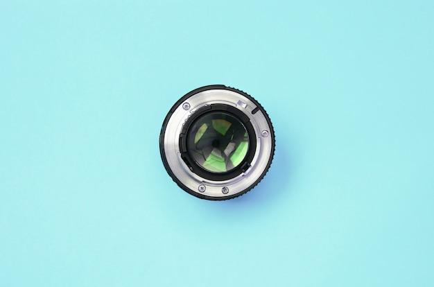 Lente da câmera com uma abertura fechada mentira na textura de papel de cor azul pastel moda