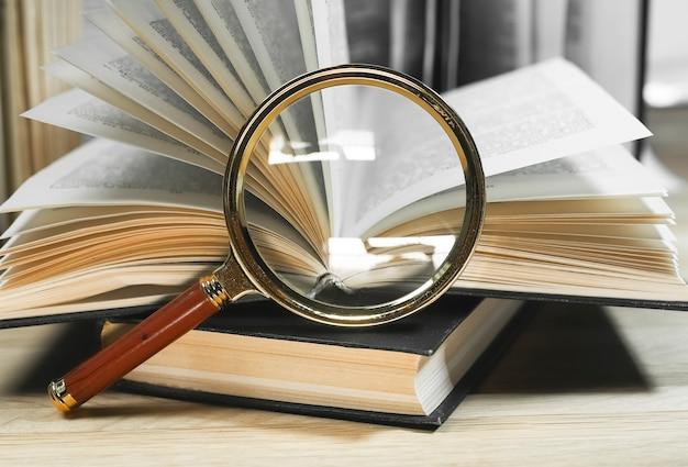 Lente de aumento e livros abertos e fechados com páginas viradas na mesa de madeira, lendo e encontrando ...
