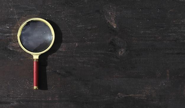 Lente de aumento em fundo escuro de madeira com espaço de cópia de banner para texto