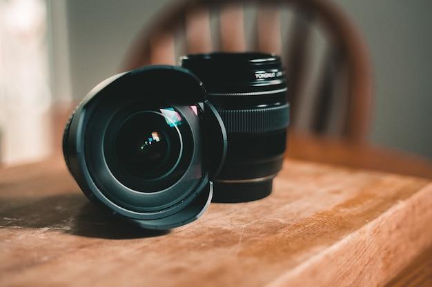 Lente de câmera dslr preta na mesa de madeira marrom