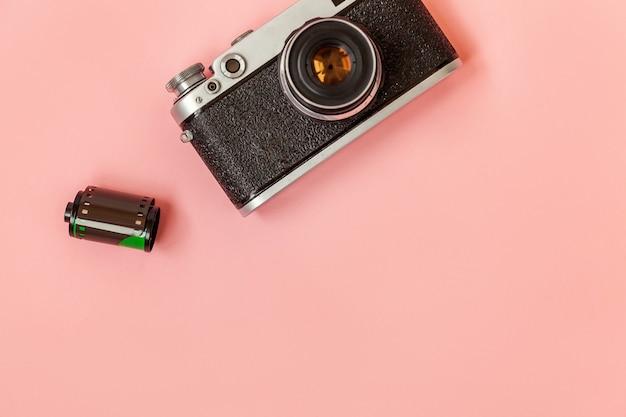 Lente de câmera fotográfica de filme vintage e rolo de filme na mesa rosa