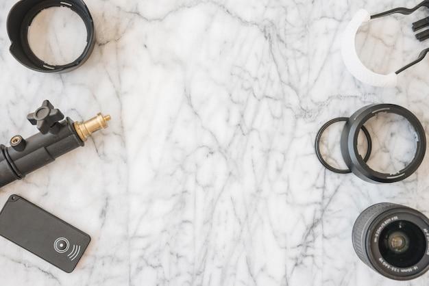 Lente de câmera moderna; anéis de extensão; tripé e acessórios em fundo de mármore