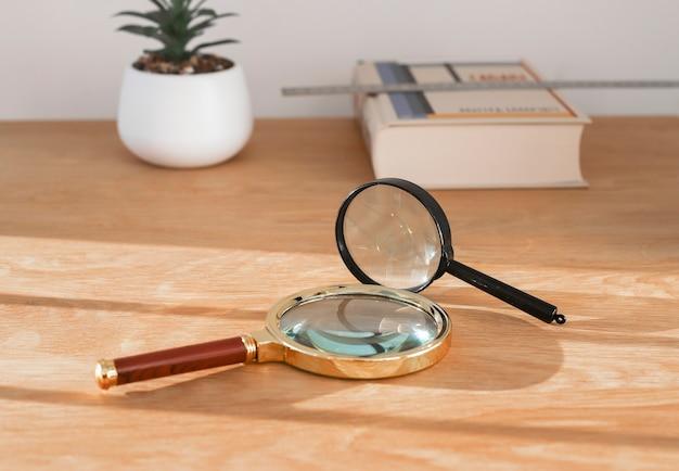 Lentes de aumento na mesa de madeira com conceito de livro de estudo de exploração e pesquisa