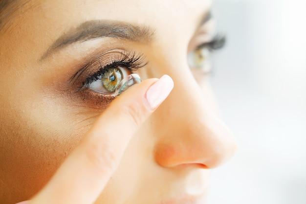 Lentes de contato da visão. closeup com rosto de mulher bonita