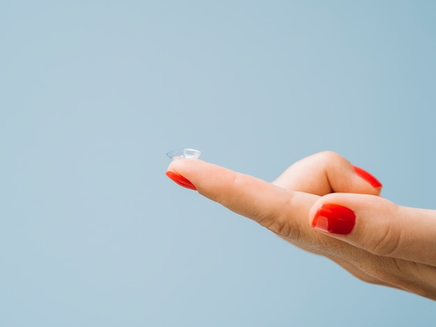 Lentes de contato em um dedo de mulher