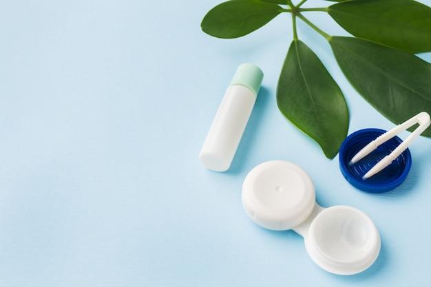 Lentes de contato, pinças e um recipiente para armazenamento de lentes