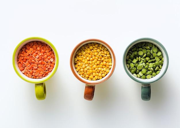 Lentilhas de diferentes tipos e cores em taças porcionadas. proteínas veganas.